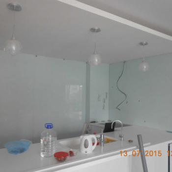 Процесс облицовки стены матовыми стеклянными панелями