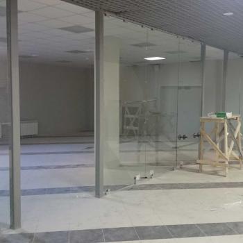 Процесс установки стеклянной перегородки в торговом центре